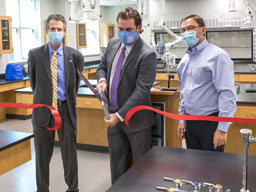Dr. Hogan, Dr. Argo and Forrest Spicher cutting ribbon in science lab.