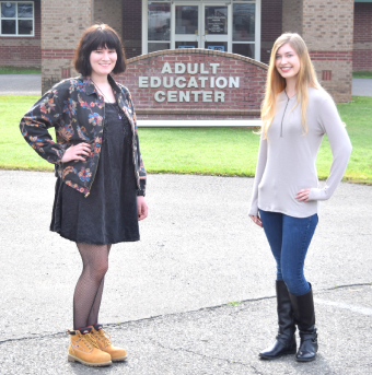 Two adult education students standing in front of the Adult Education Center for a photo.