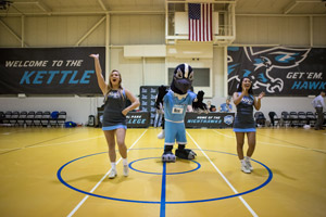 Nox the Nighthawk with team members Brooke Neel and CiCi Lopez.