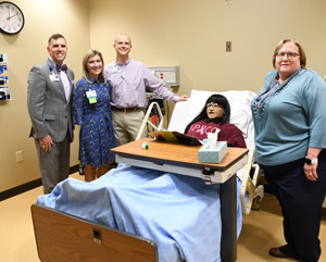 "Houston with CHI staff Rhonda Mayfield, clinical director; Dr. Brian Williams, chief nursing officer, and Janice Ivers, Dean of Nursing and Health Sciences with the ""Nursing Anne"" simulator."