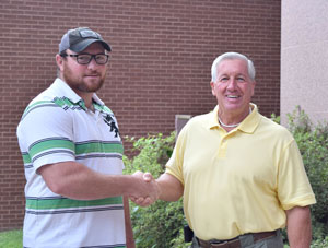 National Park College student, John Elmore, shaking hands with Lloyd's Auto Center owner, Lloyd Robertson.