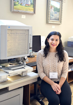 Miriam Baldwin, NPC Honor Student, sitting in front of a microfilm machine at the Garland County Historical Society.