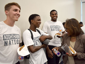 NPC Nighthawk male basketball players laughing with Joyce Craft, a memeber of the NPC Board of Trustees.