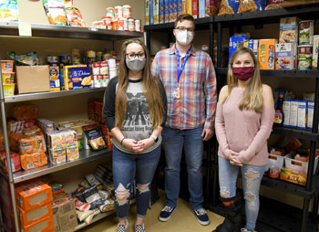 Three students standing in front of shelvs of food.