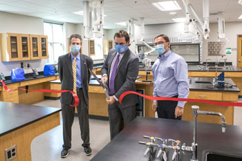 Dr. John Hogan, Dr. Charles Argo, and Forrest Spicher cutting red ribbon with oversized scissors.