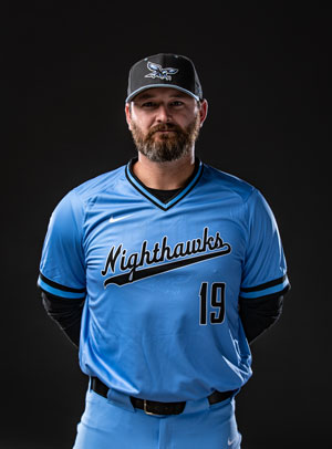 Baseball coach Rich Thompson in Nighthawk uniform in front of black background.